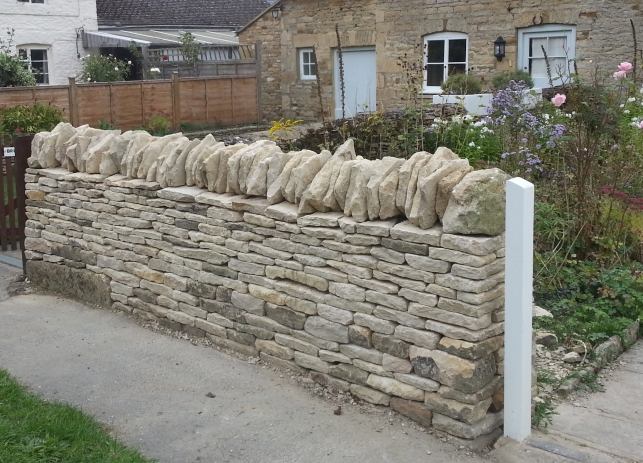 Low boundary dry stone wall in Kingham in the traditional style