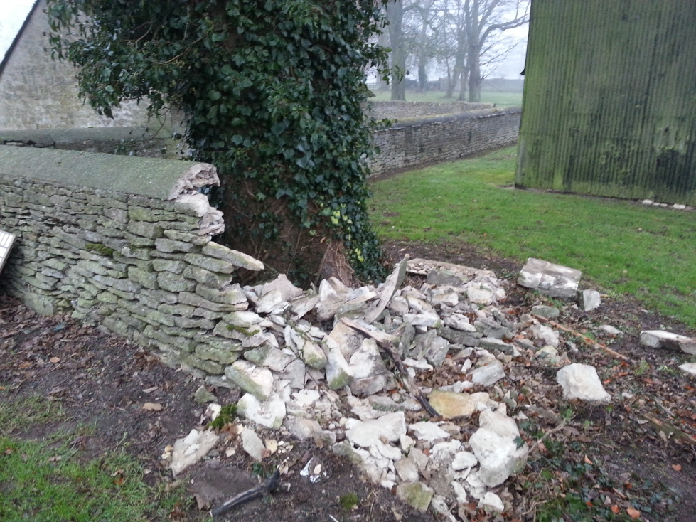 Badly damaged dry stone wall